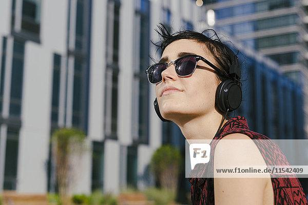 Portrait einer jungen Frau mit Kopfhörer und Sonnenbrille