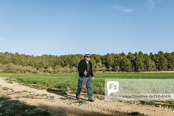 Spanien  Tarragona  Senior Mann  der mit Stöcken auf dem Feld geht