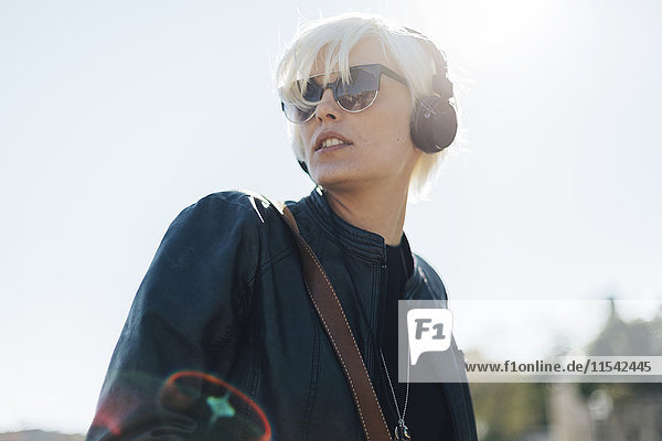 Portrait of blond woman wearing sunglasses listening music with headphones