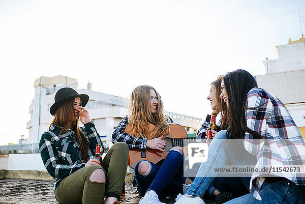 Frau spielt Gitarre auf einer Dachterrasse  während ihre Freunde zuhören.