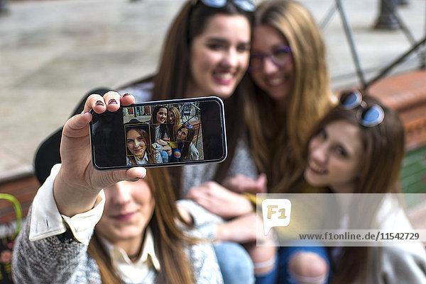 Junge Frau nimmt einen Selfie mit ihren drei Freunden  Nahaufnahme