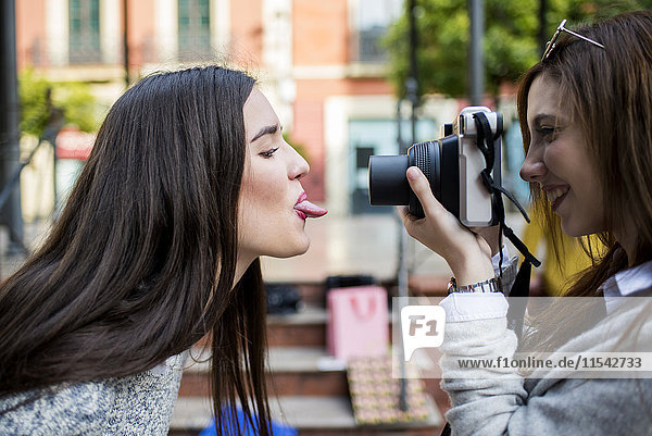 Young woman taking a picture of her friend with camera