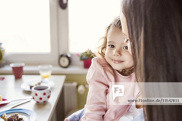 Porträt eines lächelnden kleinen Mädchens  das mit seiner Mutter kuschelt.