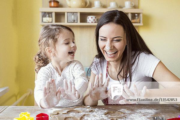 Porträt der lachenden Mutter und ihrer kleinen Tochter beim gemeinsamen Backen
