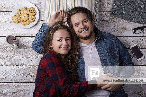 Porträt eines glücklichen jungen Paares  das sich gemeinsam auf dem Boden ausruht.