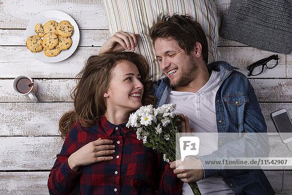 Junger Mann überrascht seine Freundin mit Blumen