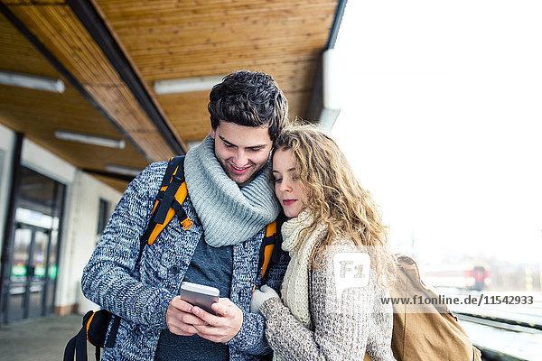 Junges Paar auf dem Bahnsteig mit Blick auf das Handy