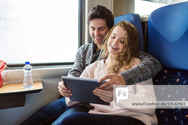 Lächelndes junges Paar im Zugwagen mit digitalem Tablett