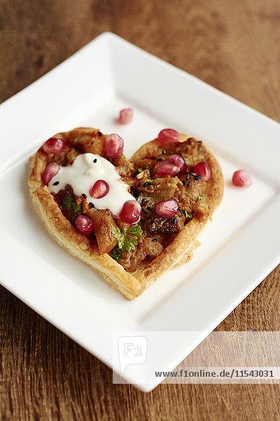 Herzförmige Blätterteigtörtchen mit Auberginen und Granatäpfeln Herzförmige Blätterteigtörtchen mit Auberginen und Granatäpfeln