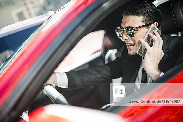 Geschäftsmann im Auto am Handy