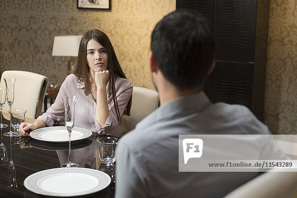 Young woman looking at man at dining table