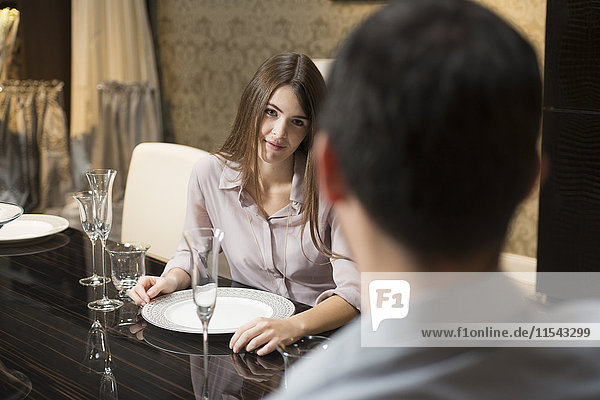 Young woman in love looking at man at dining table