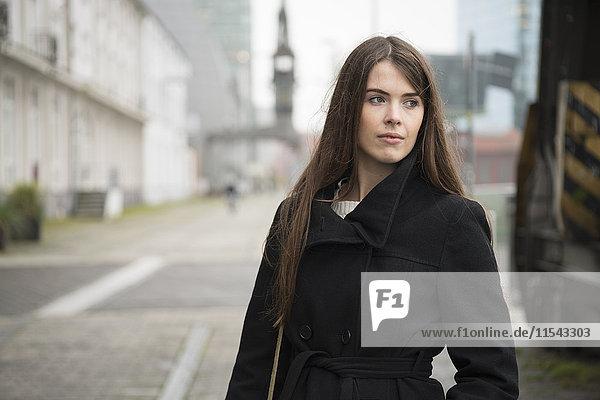 Junge Frau im schwarzen Mantel im Freien