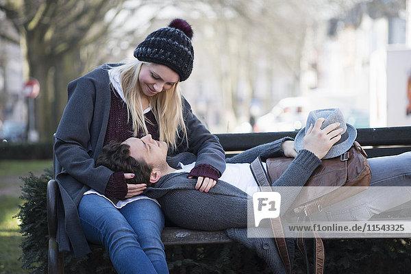 Verliebtes junges Paar auf einer Bank