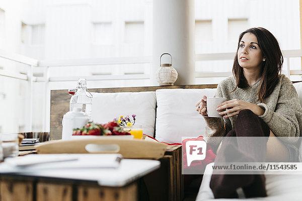 Porträt einer Frau auf dem Balkon mit Tasse Tee