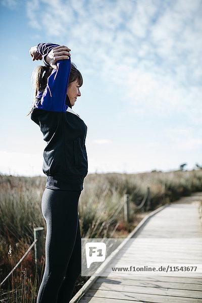 Spanien  Tarragona  Frau beim Stretching vor dem Laufen
