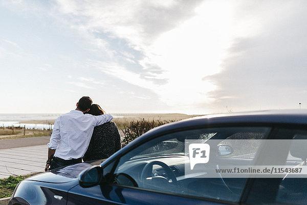 Spanien  Cubelles  Rückansicht eines jungen Paares  das auf der Motorhaube des Autos sitzt und das Meer bei Sonnenuntergang beobachtet.
