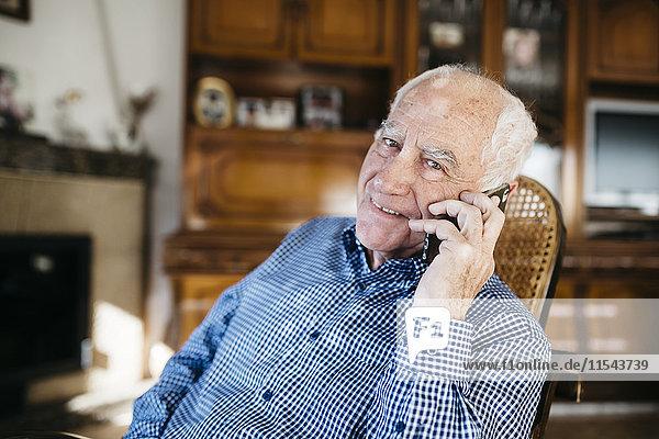 Porträt eines lächelnden älteren Mannes beim Telefonieren mit dem Smartphone zu Hause