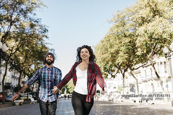 Spanien  Tarragona  glückliches junges Paar  das in der Stadt läuft