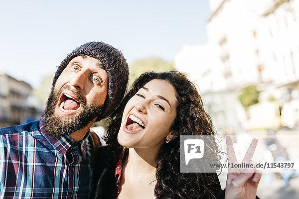 Verspieltes junges Paar zieht Gesichter
