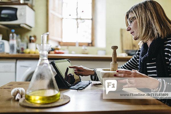 Frau mit digitaler Tablette bei der Zubereitung von Knoblauchmayonnaise in ihrer Küche