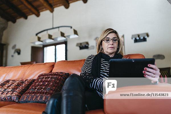 Frau sitzt auf der Couch im Wohnzimmer ihres Bauernhauses mit Hilfe eines digitalen Tabletts.