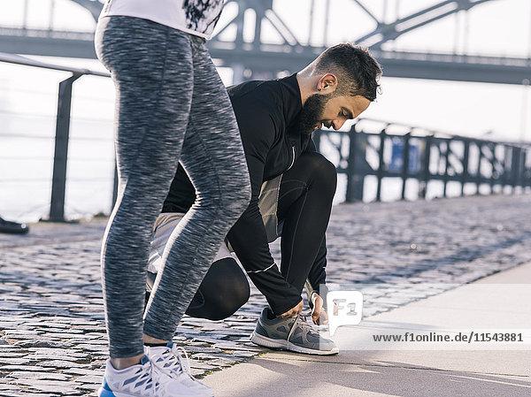 Deutschland  Köln  Junges Paar  Training  Mann beim Binden von Schuhen