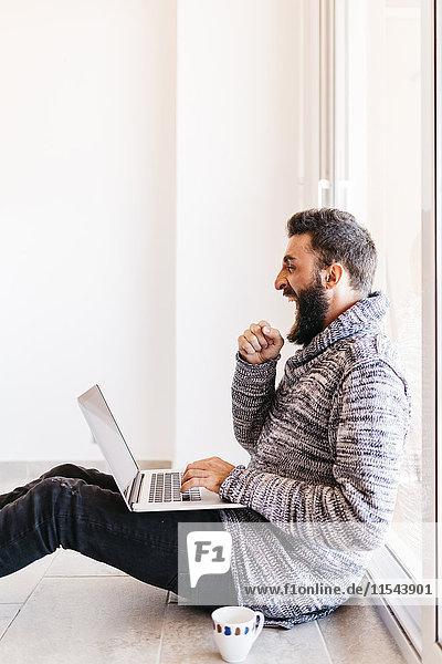 Bartiger junger Mann  der entspannt zu Hause arbeitet  auf dem Boden sitzt und den Laptop benutzt.