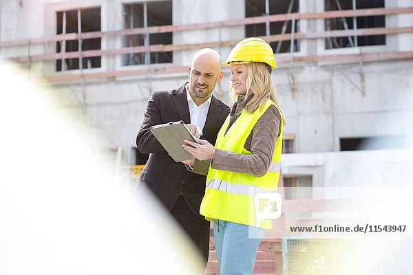 Frau mit Schutzhelm und digitalem Tablett und Mann auf der Baustelle