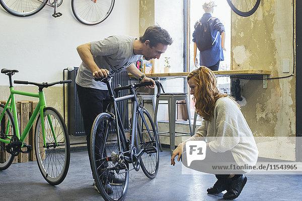 Verkäufer  der den Kunden in einem maßgeschneiderten Fahrradgeschäft berät.