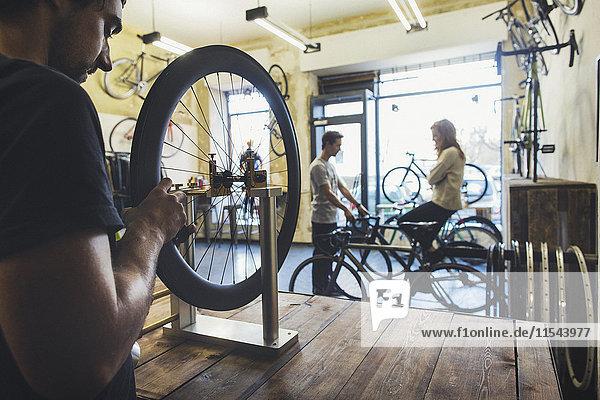 Mechaniker  Verkäufer und Kunde in einem Fahrradgeschäft nach Maß