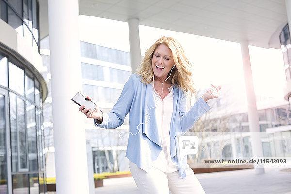 Glückliche Frau hört Musik vom Smartphone