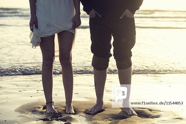 Spanien  Cádiz  Beine eines jungen Paares  das barfuß vor dem Meer steht.