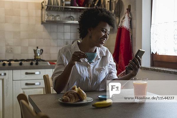 Lachende junge Frau mit Espressotasse in der Küche und Blick auf Phablet
