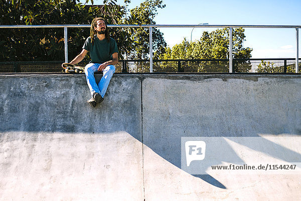Junger Mann mit Rastalocken im Skatepark