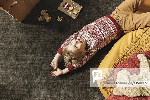 Kleiner Junge lacht und spielt auf dem Teppich mit einer Schachtel Weihnachtsdekoration