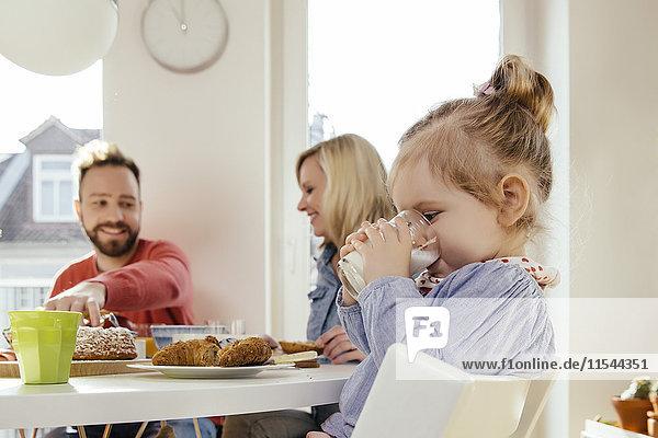 Kleines Mädchen trinkt Milch am Frühstückstisch
