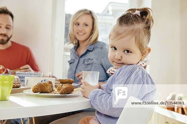 Porträt eines kleinen Mädchens mit einem Glas Milch am Frühstückstisch