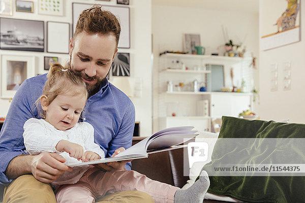 Vater und kleines Mädchen beim Lesen eines Buches zu Hause