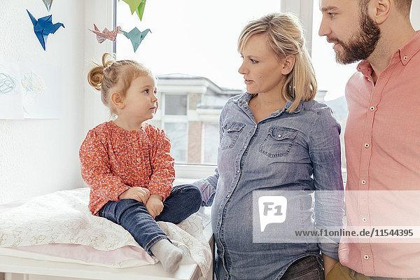 Werdende Eltern sprechen über die Schwangerschaft der Mutter mit ihrer kleinen Tochter.