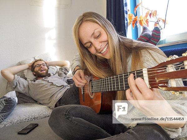 Junges Paar zu Hause beim Musizieren