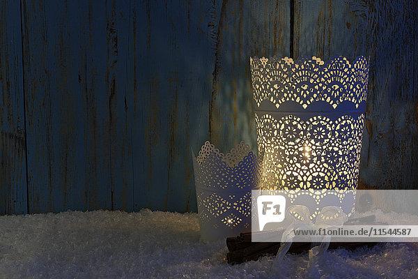 Weihnachtsdekoration mit angezündeten Kerzen  Zimtstangen und Kunstschnee