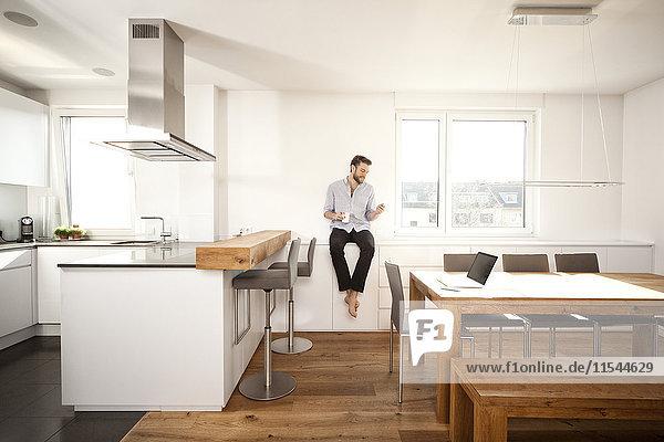 Mann mit Kaffeetasse auf Sideboard in seiner offenen Küche mit Blick auf Smartphone