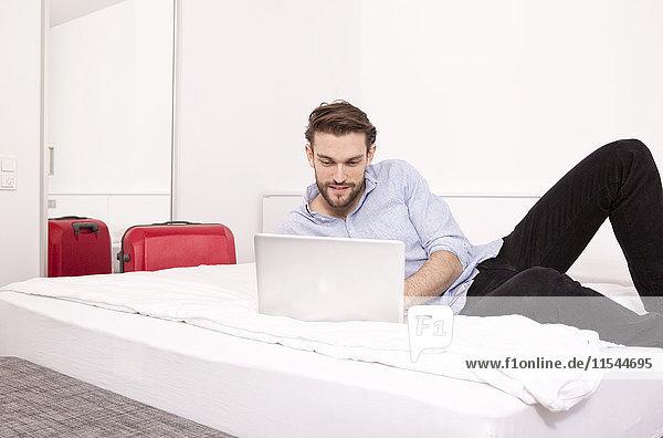 Junger Mann auf einem Hotelbett liegend mit Laptop