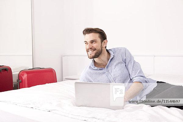 Porträt des lächelnden jungen Mannes auf Hotelbett mit Laptop