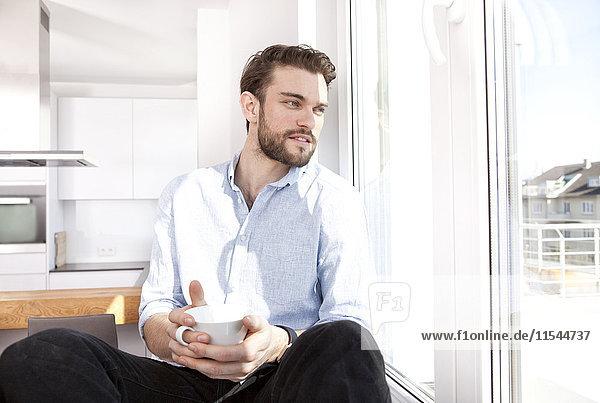Junger Mann mit Kaffeetasse auf Fensterbank sitzend durchs Fenster schauend