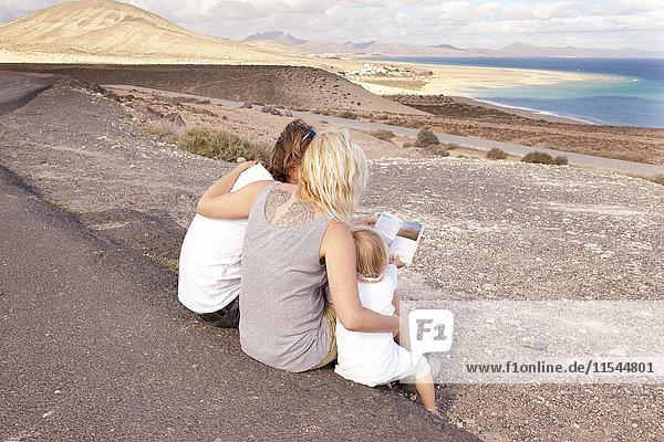 Spanien  Fuerteventura  Jandia  Familie an der Küste sitzend mit Blick in den Reiseführer