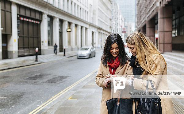 UK  London  Zwei Freunde  die die Stadt erkunden und intelligente Uhren prüfen