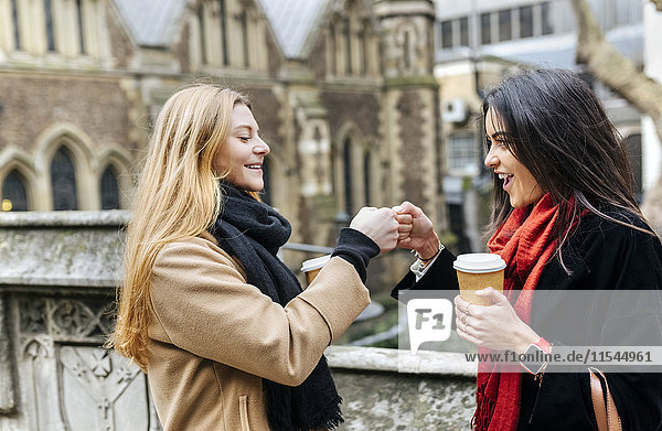 UK  London  Two friends exploring the city  drinking coffee in front of Southwark Cathedral