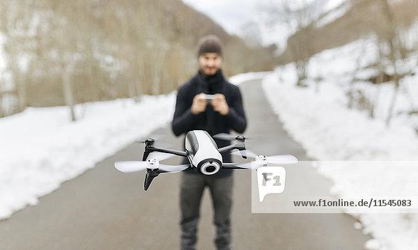 Spanien  Asturien  Mann auf einer Drohne in den schneebedeckten Bergen